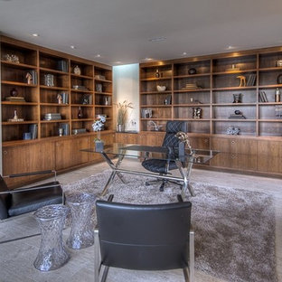 Photo of a large modern home office and library in San Diego with beige walls, limestone flooring, a freestanding desk and no fireplace.