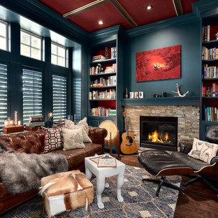バンクーバーの中サイズのトランジショナルスタイルのおしゃれなホームオフィス・書斎 (ライブラリー、青い壁、濃色無垢フローリング、標準型暖炉、石材の暖炉まわり、茶色い床) の写真