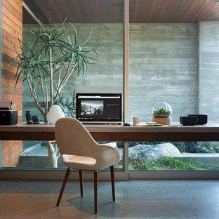 Exempel på ett modernt arbetsrum, med betonggolv och ett inbyggt skrivbord