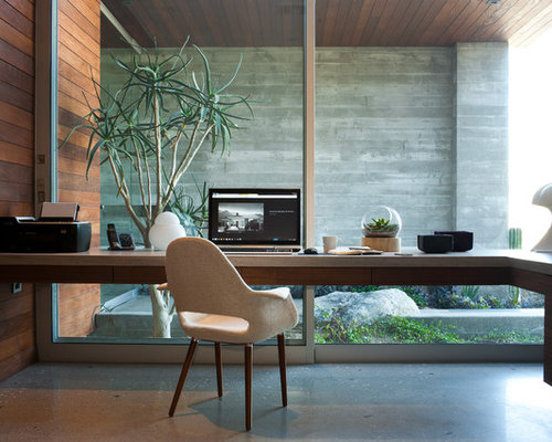 modern concrete floor home office idea in los angeles with a built in desk