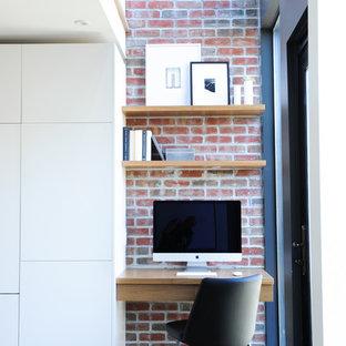 Exempel på ett modernt hemmabibliotek, med röda väggar, ljust trägolv och ett inbyggt skrivbord
