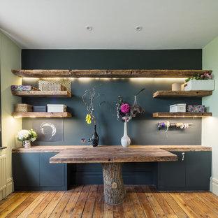 Idéer för ett mellanstort eklektiskt hobbyrum, med svarta väggar, mellanmörkt trägolv, ett inbyggt skrivbord och brunt golv