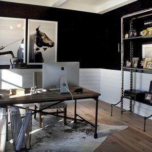 Mittelgroßes Industrial Arbeitszimmer ohne Kamin mit Arbeitsplatz, schwarzer Wandfarbe, hellem Holzboden, freistehendem Schreibtisch und braunem Boden in Sonstige
