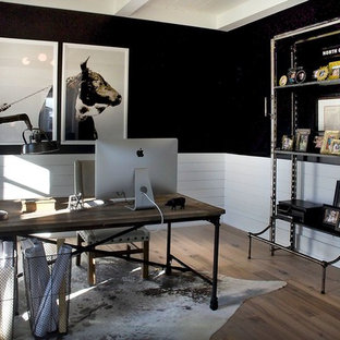 Inspiration for a mid-sized industrial freestanding desk light wood floor and brown floor study room remodel in Other with black walls and no fireplace