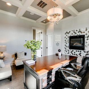 Réalisation d'un grand bureau tradition avec un mur gris, un sol en bois clair, une cheminée standard, un manteau de cheminée en carrelage, un bureau indépendant et un sol marron.