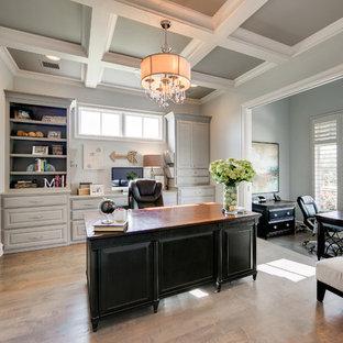 Immagine di un grande ufficio tradizionale con pareti grigie, parquet chiaro, camino classico, cornice del camino piastrellata e scrivania autoportante