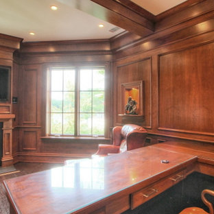 This is an example of a large traditional study in Atlanta with brown walls, vinyl flooring, a two-sided fireplace, a metal fireplace surround and a built-in desk.