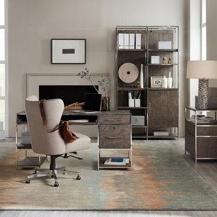 デンバーの広いコンテンポラリースタイルのおしゃれなホームオフィス・書斎 (ベージュの壁、磁器タイルの床、標準型暖炉、漆喰の暖炉まわり、自立型机、グレーの床) の写真