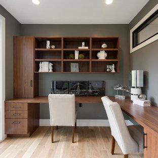 Imagen de despacho moderno, pequeño, con paredes grises, suelo de madera clara y escritorio empotrado