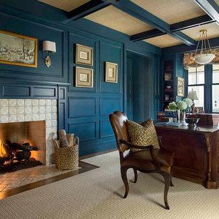 Cette image montre un bureau traditionnel avec un mur bleu, une cheminée standard, un manteau de cheminée en carrelage, un bureau indépendant et moquette.