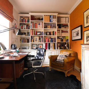 Неиссякаемый источник вдохновения для домашнего уюта: маленькое рабочее место в классическом стиле с оранжевыми стенами, отдельно стоящим рабочим столом и паркетным полом среднего тона без камина