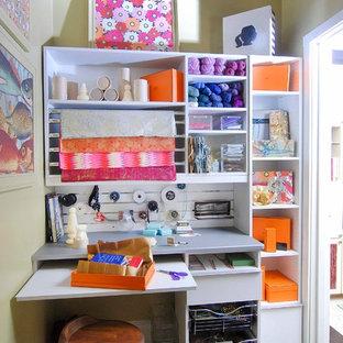Foto på ett mellanstort funkis hobbyrum, med gula väggar, mörkt trägolv och ett inbyggt skrivbord