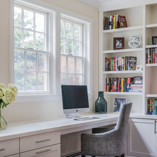 Foto på ett vintage hemmabibliotek, med ett inbyggt skrivbord, beige väggar, mörkt trägolv, en standard öppen spis, en spiselkrans i sten och brunt golv