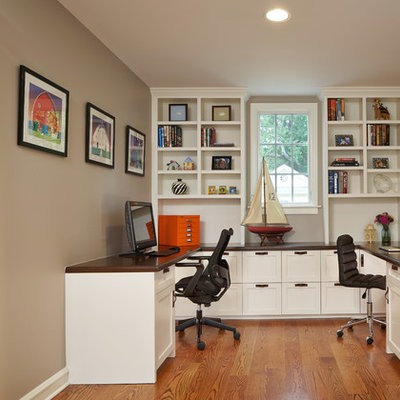 Home office - mid-sized traditional built-in desk medium tone wood floor and brown floor home office idea in Chicago with beige walls and no fireplace