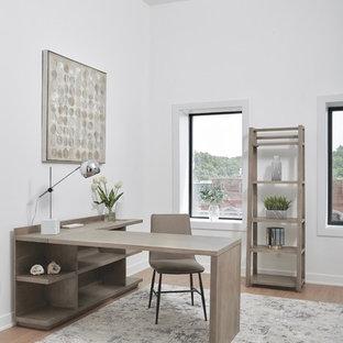Стильный дизайн: большое рабочее место в современном стиле с белыми стенами, отдельно стоящим рабочим столом и полом из винила - последний тренд