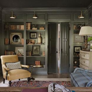 Lantlig inredning av ett hemmabibliotek, med gröna väggar, mörkt trägolv, ett fristående skrivbord och brunt golv