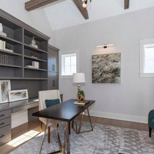 Inspiration för stora lantliga arbetsrum, med ett bibliotek, vita väggar, ljust trägolv, ett fristående skrivbord och brunt golv