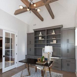Lantlig inredning av ett stort arbetsrum, med ett bibliotek, vita väggar, ljust trägolv, ett fristående skrivbord och brunt golv