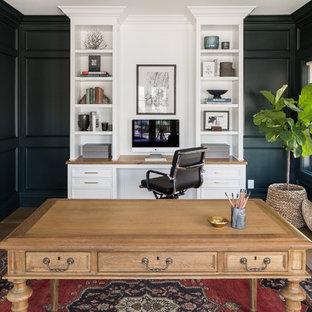 Cette image montre un bureau rustique avec un mur noir, un sol en bois brun, une cheminée standard, un manteau de cheminée en pierre, un bureau intégré et un sol marron.
