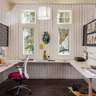 Example of a large minimalist built-in desk concrete floor and gray floor craft room design in Boston with white walls