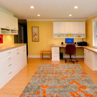 Aménagement d'un grand bureau contemporain de type studio avec un mur jaune, un sol en bois clair et un bureau intégré.
