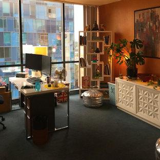Esempio di un grande atelier minimalista con pareti arancioni e moquette