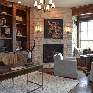 Immagine di un grande ufficio design con pareti beige, camino ad angolo, cornice del camino in pietra, scrivania autoportante e parquet scuro