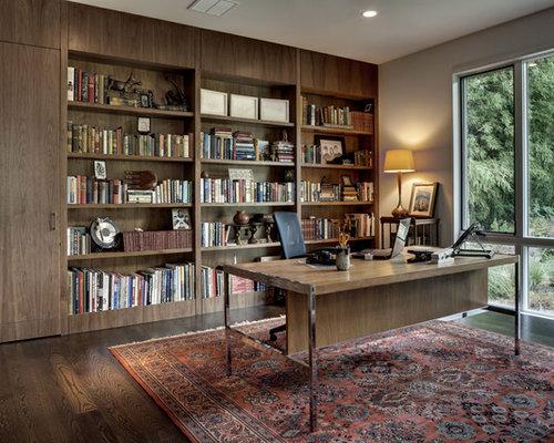 Trendy freestanding desk dark wood floor home office photo in Dallas with  gray walls