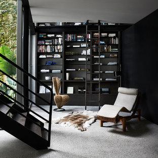 Foto di uno studio minimal con libreria, pareti nere, pavimento in cemento e pavimento grigio