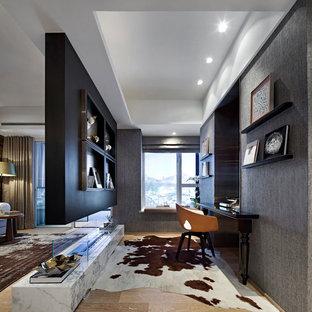 ニューヨークのコンテンポラリースタイルのおしゃれな書斎 (グレーの壁、淡色無垢フローリング、両方向型暖炉、造り付け机、ベージュの床) の写真