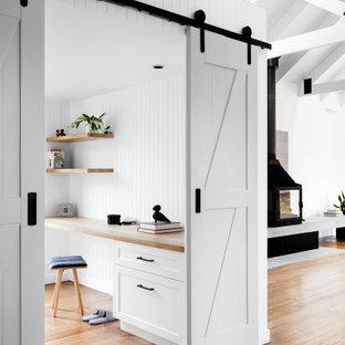 На фото: маленькое рабочее место в современном стиле с белыми стенами, паркетным полом среднего тона, печью-буржуйкой, фасадом камина из бетона, встроенным рабочим столом, сводчатым потолком и панелями на части стены с