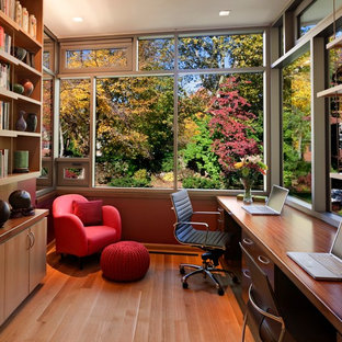 Ejemplo de despacho actual, de tamaño medio, sin chimenea, con suelo de madera en tonos medios, escritorio empotrado y suelo marrón