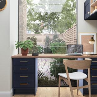 Exempel på ett litet klassiskt hemmabibliotek, med vita väggar, laminatgolv och ett inbyggt skrivbord
