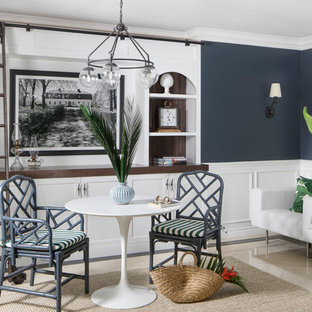 マイアミの中くらいのビーチスタイルのおしゃれなホームオフィス・書斎 (ライブラリー、白い壁、トラバーチンの床、自立型机、ベージュの床) の写真