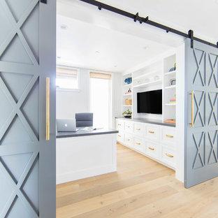 Modelo de despacho de estilo de casa de campo, de tamaño medio, con paredes blancas, suelo de madera en tonos medios, escritorio empotrado y suelo beige