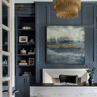 Inredning av ett klassiskt mycket stort hemmabibliotek, med blå väggar, mellanmörkt trägolv, en standard öppen spis, en spiselkrans i sten, ett fristående skrivbord och brunt golv