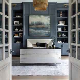 Geräumiges Klassisches Arbeitszimmer mit Arbeitsplatz, blauer Wandfarbe, braunem Holzboden, Kamin, Kaminsims aus Stein und freistehendem Schreibtisch in Houston