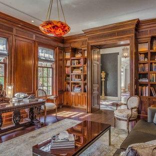 Idee per un grande studio classico con libreria, pareti marroni, parquet scuro, camino classico, cornice del camino in pietra, scrivania autoportante e pavimento marrone