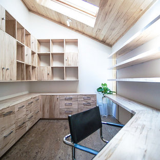 Foto på ett mellanstort funkis hemmastudio, med vita väggar, korkgolv, ett inbyggt skrivbord och brunt golv