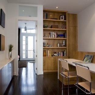 Inredning av ett modernt arbetsrum, med vita väggar, mörkt trägolv, ett inbyggt skrivbord och svart golv