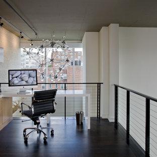 Foto di uno studio industriale con pareti bianche, parquet scuro e scrivania incassata