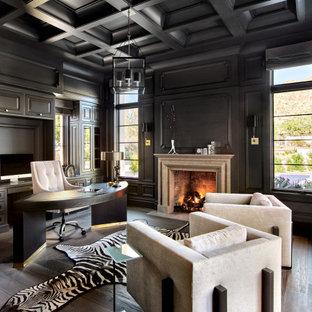 Modelo de despacho casetón y panelado, mediterráneo, panelado, con escritorio independiente, paredes negras, suelo de madera oscura, chimenea tradicional, suelo marrón y panelado