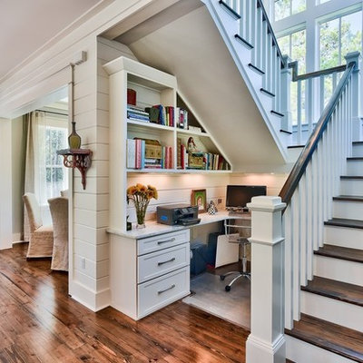Example of a beach style built-in desk dark wood floor home office design in Miami with white walls