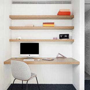 Cette photo montre un bureau moderne avec un mur blanc, moquette, un bureau intégré et un sol bleu.