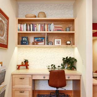 Foto på ett rustikt hemmabibliotek, med vita väggar, ett inbyggt skrivbord, mellanmörkt trägolv och brunt golv