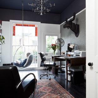 Immagine di uno studio chic con pareti nere, scrivania autoportante e pavimento nero