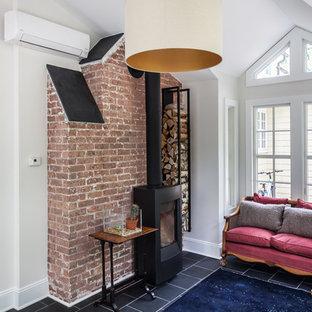 ニューヨークの中サイズのトラディショナルスタイルのおしゃれなアトリエ・スタジオ (グレーの壁、スレートの床、薪ストーブ、自立型机) の写真