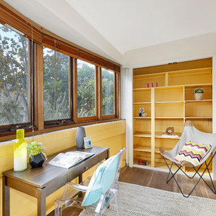 Idee per uno studio minimalista di medie dimensioni con pavimento in compensato, nessun camino, pavimento marrone, pareti gialle e scrivania autoportante