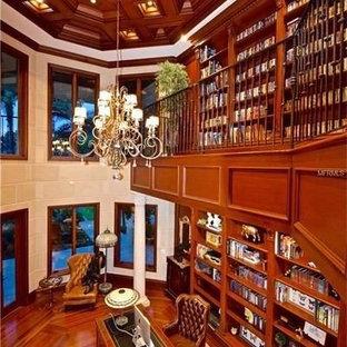 Aménagement d'un très grand bureau classique avec un mur marron, un sol en bois brun, un manteau de cheminée en pierre et un bureau indépendant.