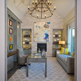 Ejemplo de estudio clásico renovado, grande, con paredes grises, chimenea tradicional, escritorio independiente, suelo de madera oscura, marco de chimenea de piedra y suelo gris